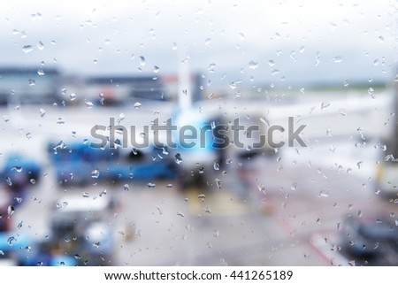 Abstract defocused bokeh of airplane at airport gate with sun coming out after the rain. Modern travel concept and wander lifestyle at sunset. Focus on raindrops with warm vintage filtered look - stock photo