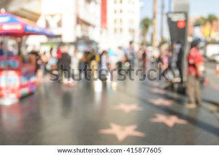 Abstract defocused bokeh view of artist stars and everyday multiracial people around the world famous Walk Of Fame in late afternoon on Hollywood Boulevard in LA California - United States of America - stock photo