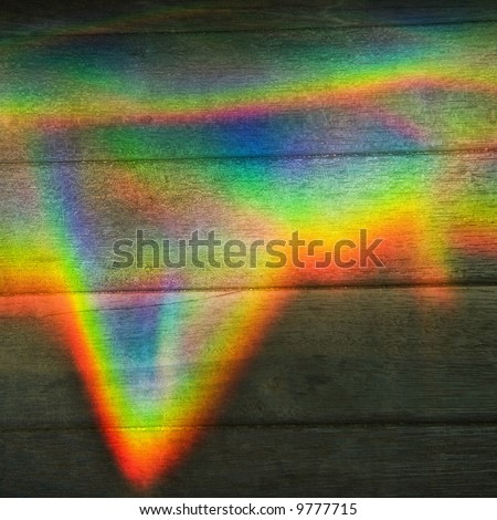 Abstract design of rainbow color prism on wood paneling. - stock photo