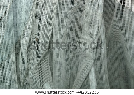Abstract detail of a broken window and sharp edges of glass with a curtain in the background. - stock photo
