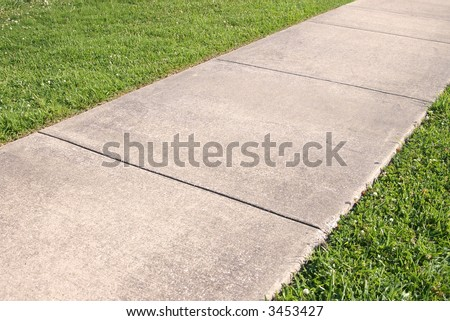 Abstract detail of a concrete sidewalk and grass - stock photo