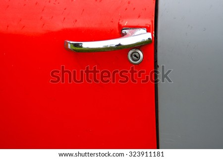 Abstract detail of old truck door with red and grey panels and chrome door handle - stock photo