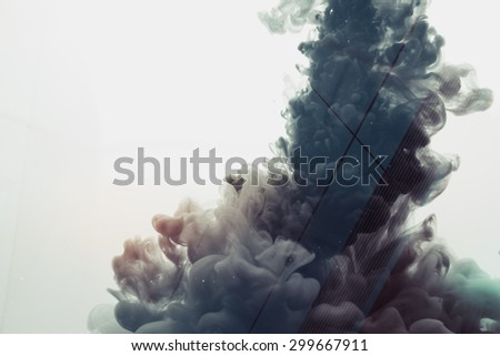 Abstract double exposure image of inks in water with business building