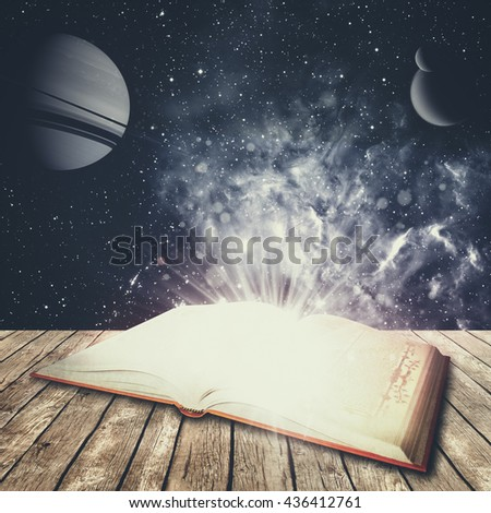 Abstract education and science backgrounds with opened book over desk. NASA imagery used  - stock photo