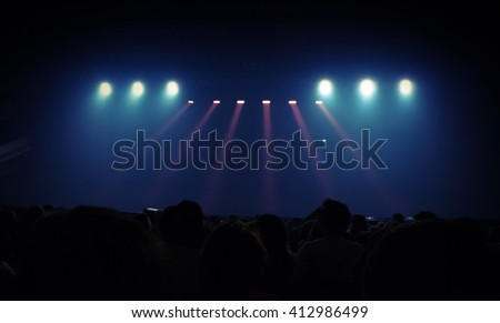 Abstract entertainment event background. Blurred photo with spotlights scene illumination. Spectators watch the stage