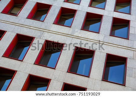 Abstract fragment of modern building facade with red window frames