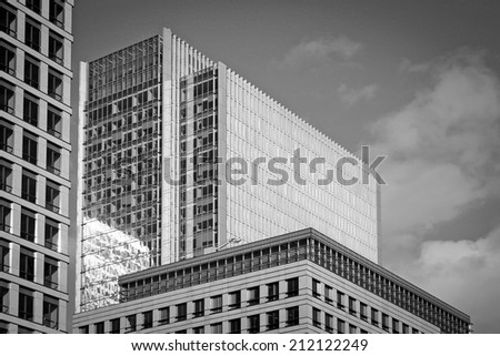 Abstract, full-frame modern business buildings.  Black and white with film grain added. - stock photo