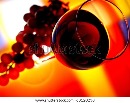 Abstract  glassware background design of wine glass and grapes  on multicolored  background. - stock photo
