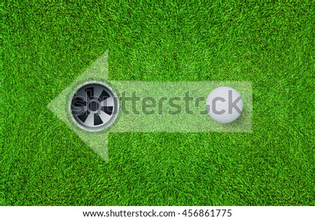 Abstract  golf ball and golf hole on green grass texture background with direction symbol.