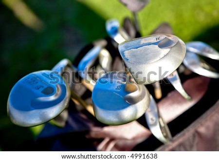 abstract golf clubs with green grass in the background - stock photo