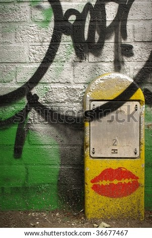 Abstract Graffiti Detail on a Brick Wall and Public Utilities Sign - stock photo