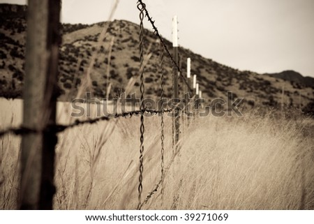 Abstract, grainy, old style sepia barbed wire fence in grassland with hills in the background - stock photo