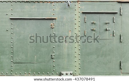 Abstract green industrial metal background texture with manholes, bolts and rivets, details of Russian armored train from WWII time - stock photo