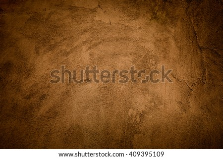 Abstract grunge yellow-brown background with spot light in center of frame and darkened edges, vintage background rough texture