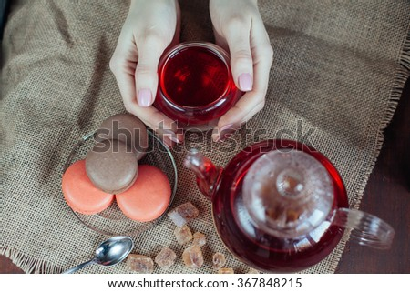 Abstract hands holding cup of tea and Colorful macaroons, teapot on wooden background.top view