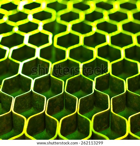 Abstract hexagonal structure with shallow dof. Green metal honeycomb mesh. Technology concept. - stock photo