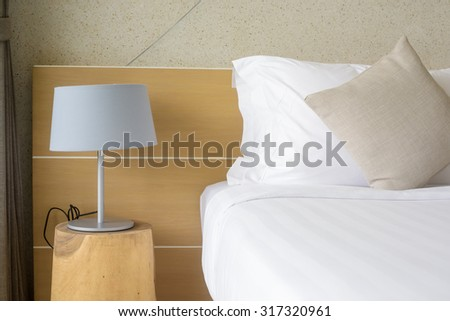 Abstract hotel bedroom with lamp and hotel bed with space for text