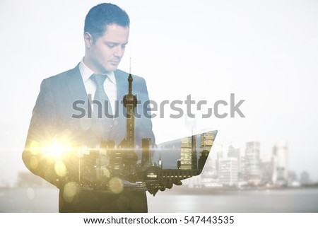 Abstract image of caucasian guy using laptop on city background. Double exposure. Communication concept