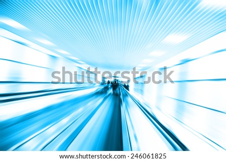 Abstract image of moving walkway and blurred people on background. - stock photo
