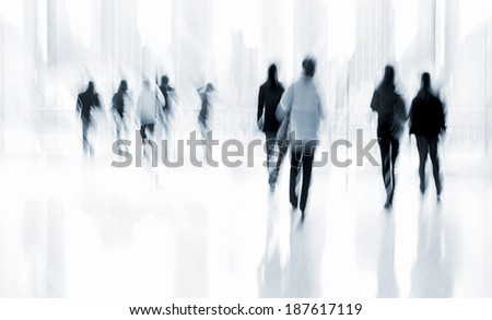 abstract image of people in the lobby of a modern business center with a blurred background and blue tonality