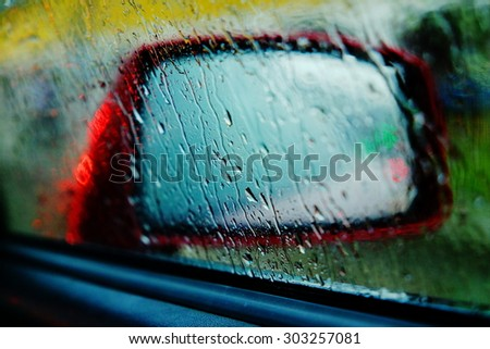 Abstract image of rain drops on a red car side view mirror and window, close up - stock photo