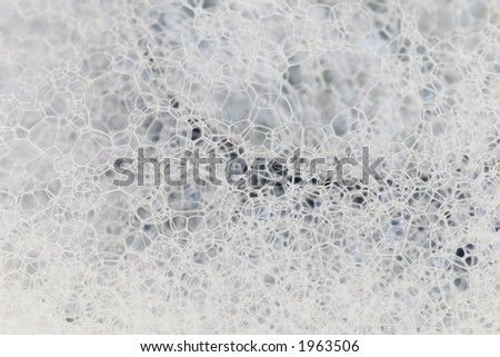 Abstract image of soap bubbles gathered around the drain in the sink. - stock photo