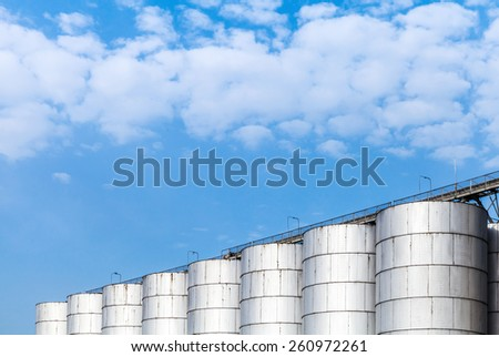 Abstract industrial architecture fragment on blue sky background, shining metal tanks for storage of bulk materials - stock photo