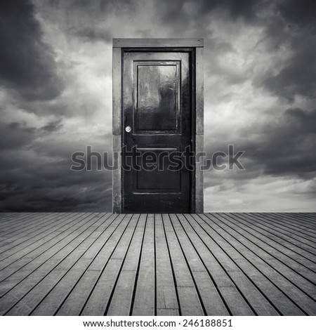 Abstract interior concept with old black door, wooden floor and dramatic sky  - stock photo