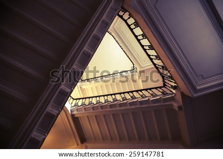 Abstract interior fragment, triangle shaped flight of stairs, looking up. Vintage toned photo with instagram style filter effect - stock photo