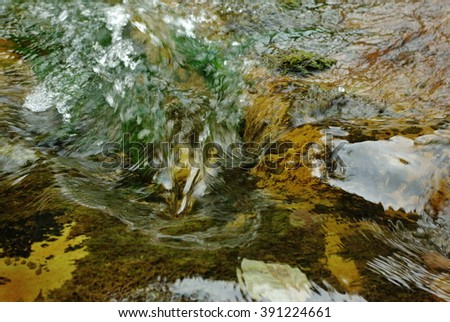 Abstract landscape of the fast flowing water in the mountain river. Light reflection on the turbulent water flow. Flowing water  illuminated by reflected color from sunlit trees and blue sky overhead. - stock photo