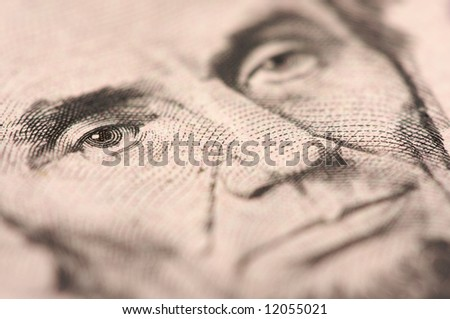 Abstract Macro of U.S. Five Dollar Bill's Abraham Lincoln face with Narrow Depth of Field. - stock photo