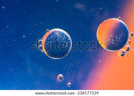 Abstract macro with oil drops in water, looking like planets in space. - stock photo