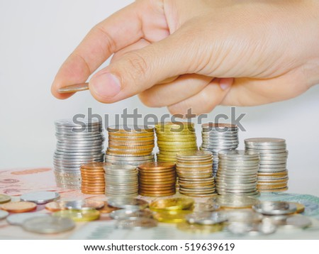 abstract money saving hand put a coin on stacking coins
