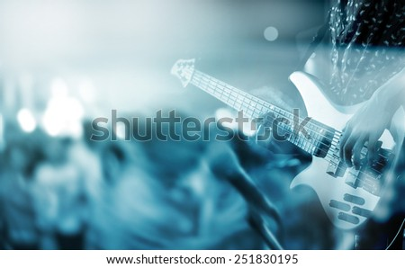 abstract motion blur guitarist on stage and people dance in floor, blue tone and blur concept - stock photo