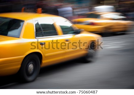 Abstract motion blur of a city street scene with a yellow taxi cabs speeding by. - stock photo