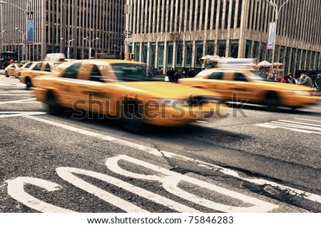 Abstract motion blur of a city street scene with a yellow taxi cabs speeding bY - stock photo
