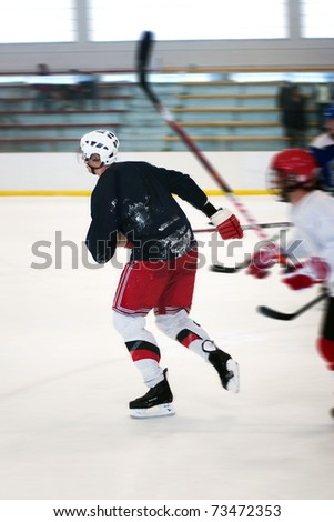 Abstract motion blur of two hockey players skating down the ice rink. - stock photo