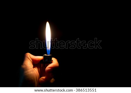 abstract Motion Hand with lighter igniting sparks on dark background  - stock photo