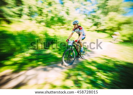 Abstract motions blur background of mountain Bike cyclist riding track in forest. - stock photo