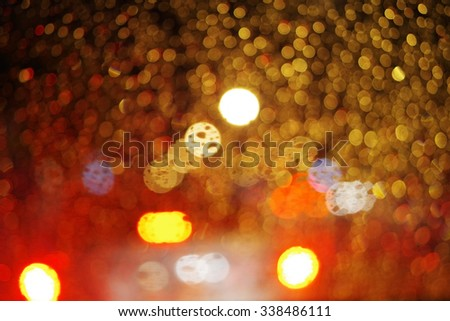 Abstract night city light and bokeh through car windscreen covered in rain, defocussed background - stock photo