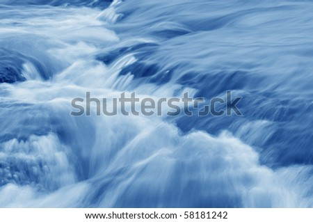 Abstract of a swiftly moving stream in shade of blue. - stock photo