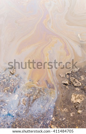Abstract of an industrial chemical oil spill on the water surface releasing streaks of hazardous pollutants into the environment. - stock photo