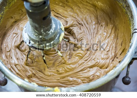 Abstract of chocolate cake batter being mixed in an electric mixer. Extreme shallow DOF with focus on wire mixer. - stock photo
