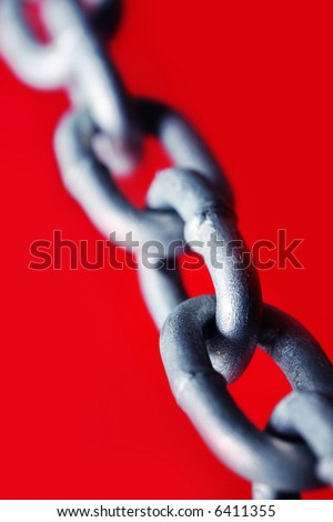 Abstract of galvanized chain links, with vibrant red background.  Shallow DOF. - stock photo