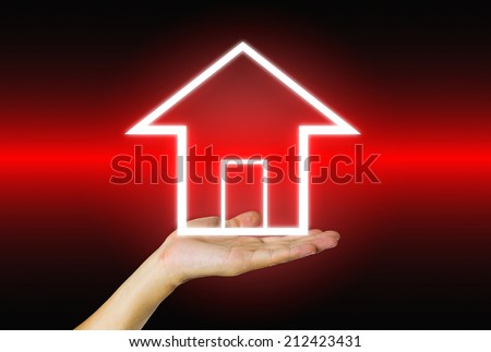 Abstract of home in hand on dark background. - stock photo