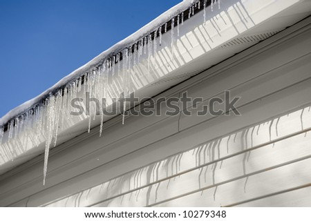 Abstract of Icicles melting on the roof against a clear blue sky.