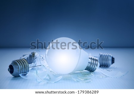 abstract of led light bulb glowing and lying with another broken bulb use for idea and creative symbol - stock photo