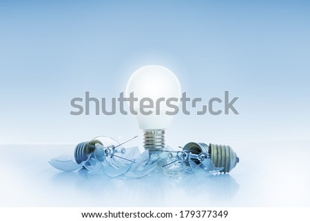 abstract of led light bulb glowing on light blue background with another broken on ground use for idea and creative symbol - stock photo