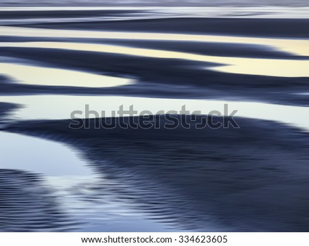 Abstract of luminous tide pools on sandy beach at sunset along the Pacific coast of Olympic Peninsula in Washington, USA, for themes of nature, serenity, the environment (one of a series) - stock photo