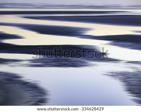 Abstract of luminous tide pools on sandy beach near sunset along the Pacific coast of Olympic Peninsula in Washington, USA, for themes of nature, serenity, the environment (one of a series) - stock photo